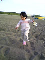 砂浜で遊ぶ娘